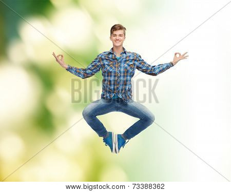 happiness, freedom, movement, ecology and people concept - smiling young man hanging of flying in air in pose of yoga over green background