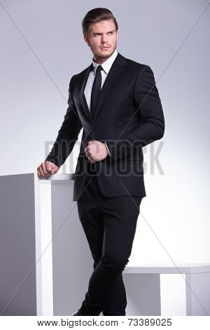 Portrait of a young handsome business man leaning on a white table while holding one hand on his jacket, looking away from the camera.