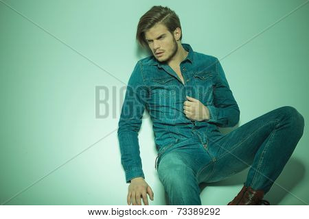 Picture of a handsome fashion man looking away from the camera while siiting on the floor, pulling his shirt.