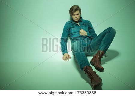 Full body picture of a young fashion man lying on studio background, looking at the camera while pulling his jeans shirt. Vintage look picture.
