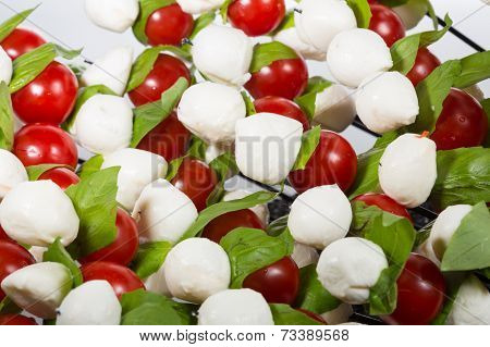 Appetizer. baby mozzarella with cherry tomatoes and basil leaves.
