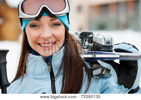 Close up of woman wearing sports jacket and goggles who hands skis
