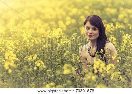 Beautiful Woman In Meadow Of Yellow Flowers Sitting Down