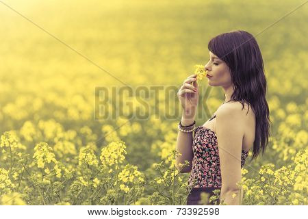 Beautiful Woman In Meadow Of Yellow Flowers Sniffing Flower