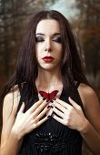 stock photo of gothic girl  - Lovely young girl with closed eyes holds a red butterfly in hands - JPG
