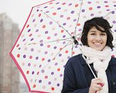 pic of hispanic  - Hispanic woman walking in city with umbrella - JPG