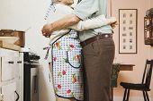 image of adoration  - Senior couple hugging in kitchen - JPG