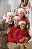stock photo of pre-adolescents  - Hispanic family wearing Santa Claus hats - JPG