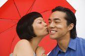stock photo of chums  - Asian woman kissing boyfriend on cheek - JPG