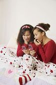 stock photo of identical twin girls  - African twin sisters looking at cell phones - JPG