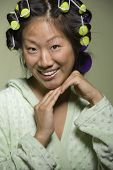 stock photo of coy  - Asian woman with curlers in hair - JPG