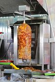 stock photo of gyro  - Kebab gyro meat roasted on a vertical spit