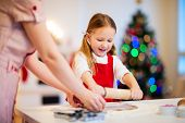 picture of christmas cookie  - Family of mother and daughter baking gingerbread cookies at home on Christmas eve - JPG