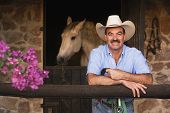 image of reign  - Hispanic man in front of stable - JPG