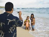 picture of pacific islander ethnicity  - Pacific Islander father taking photograph of family - JPG