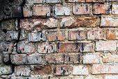 stock photo of mortar-joint  - The old cracked brick wall stained with black tar - JPG