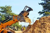 stock photo of wheel loader  - Wheel loader Excavator unloading sand with water during earth moving works at construction site - JPG