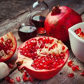 stock photo of naturopathy  - Pomegranate and bottles of essence or tincture on wooden rustic table - JPG