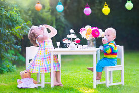 picture of little sister  - Two happy children cute curly toddler girl and a little baby boy brother and sister enjoying a tea party with their toys playing with dishes cup cakes and muffins in a sunny summer garden