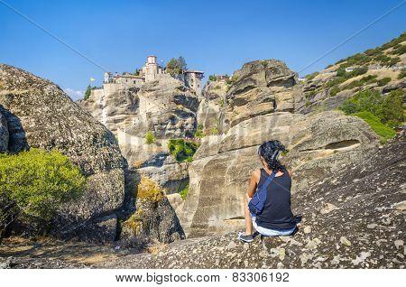 Girl relaxing in front of the Meteora monasteries, Greece