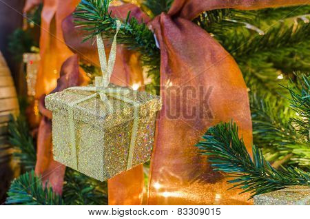 Gold gift box hanging on a Christmas tree with red ribbon
