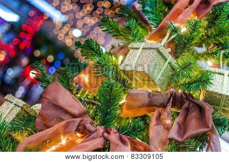Gifts hanging on a Christmas tree with red ribbons