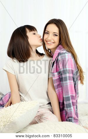 Two girls in pajamas sitting on fluffy white carpet, on light background