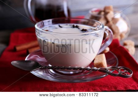 Black tea with milk and lump sugar in glassware on color wooden planks background