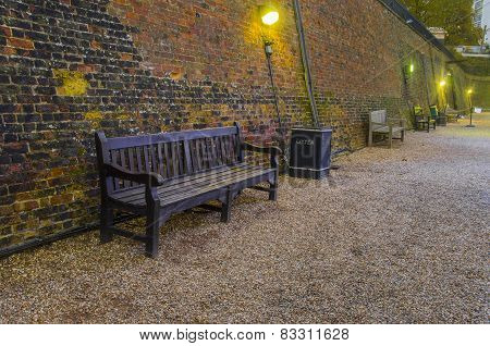 Old wooden benches in old alley with brick wall