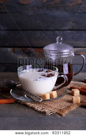 Black tea with milk in glassware and lump sugar on color wooden planks background