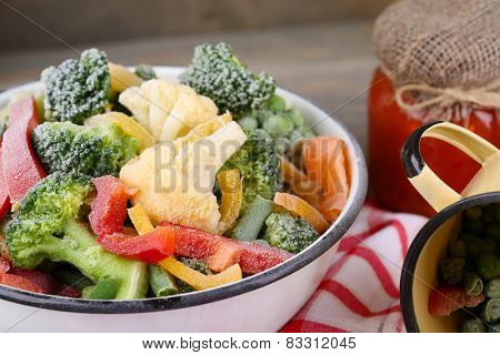 Frozen vegetables in bowl and mug on napkin, on wooden table background