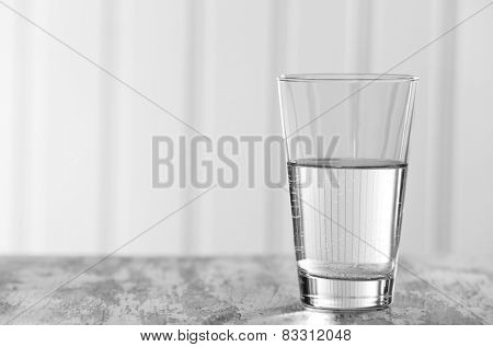 Glass of clean mineral water on old color wooden surface and planks background