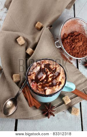 Cup of hot coffee with marshmallow on fabric with lump sugar, cinnamon, star anise and stainer of cocoa on color wooden planks background