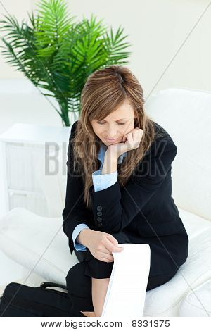 Thoughtful Caucasian Businesswoman Sitting On A Sofa Holding A Paper
