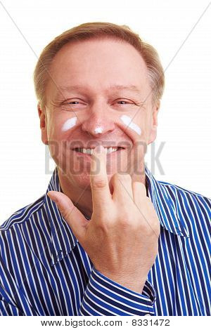 Man Putting Blob Of Lotion On His Nose