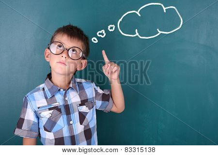 Schoolboy at blackboard in classroom and text cloud with space for your text