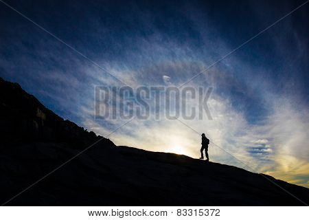 Woman Walking On Mountain Silouhetted By Sunrise Or Sunset