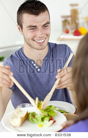 Happy  Man Putting Salad On A Plate Having Dinner With His Girlfriend