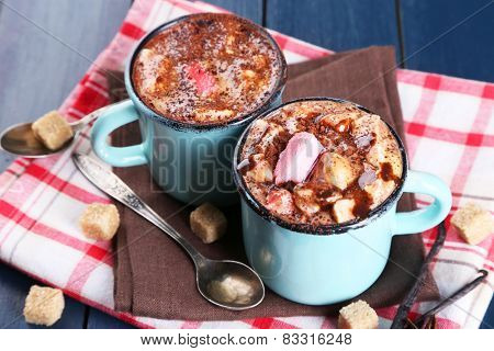 Mugs of hot coffee with marshmallow on napkin with lump sugar, star anise and vanilla sticks on color wooden table background