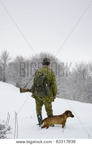 Male hunter with hunter rifle walking in the snow eith his dog