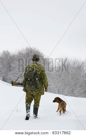 Hunter with his dog in forest on snow