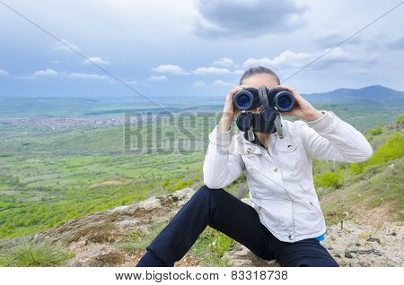 Successful girl with binocular on a mountain