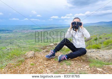 young girl looks with binoculars on a peak