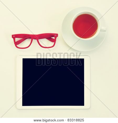 high-angle shot of a table with a pair of red plastic-rimmed eyeglasses, a tablet computer and a cup of tea