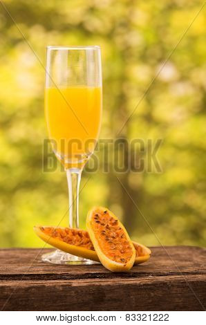 glass of juice with banana passionfruit slices on a wooden table