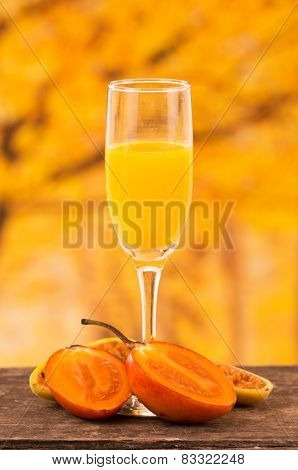 glass of juice with tree tomato and banana passionfruit slices on a wooden table