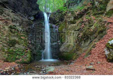Small waterfall in the forest in autumn