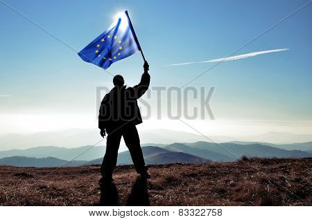 Successful man waving European Union flag on a mountain top