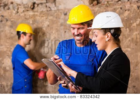 Builder and supervisor on construction site discussing over plans