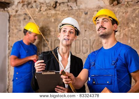 Builder and architect discussing on construction site, he is holding a folding rule pointing with it